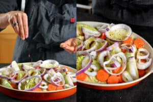 A person in a gray apron is adding seasoning to a casserole pan filled with cabbage wedges, carrots, and onions.