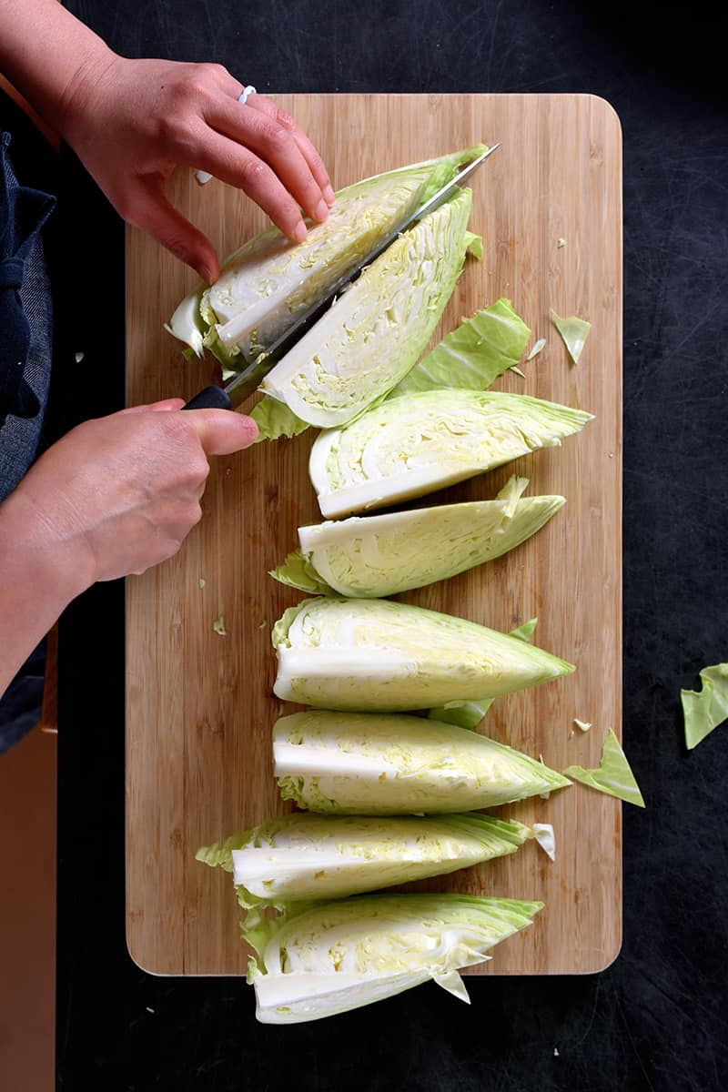 An overhead shot of someone cutting up a green cabbage into 8 wedges on a wooden cutting board