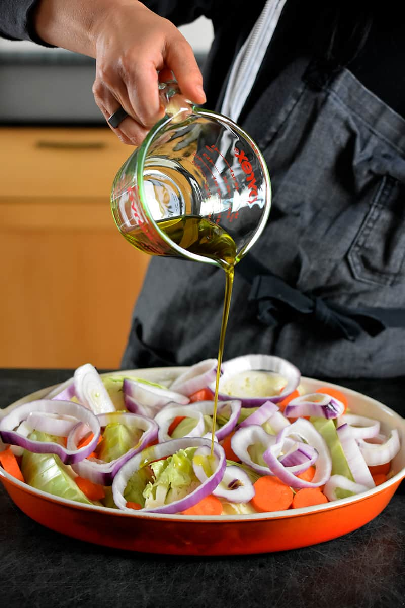 Someone in a gray apron is pouring olive oil from a liquid measuring cup onto a casserole pan filled with cabbage wedges, carrots, and onions.
