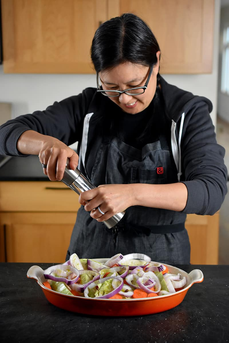 An Asian woman in glasses is adding freshly ground black pepper from a Peppermill to a casserole pan filled with cabbage wedges, carrots, and onions.