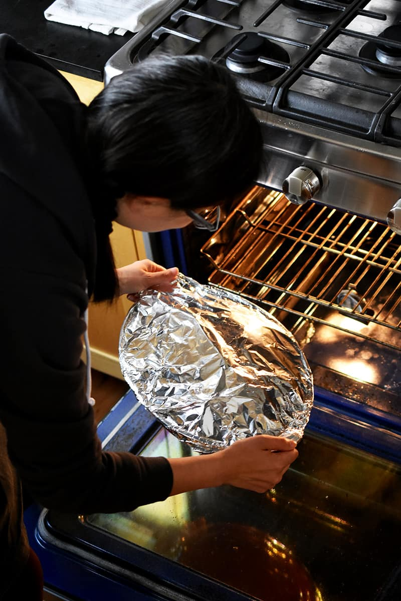 A brunette woman is placing a foil covered casserole pan filled with braised cabbage into an open oven
