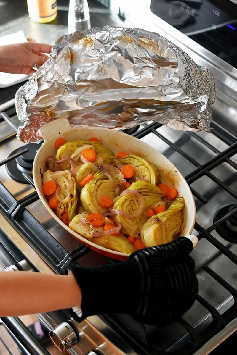 Removing foil from a casserole pan filled with braised cabbage out of the oven.