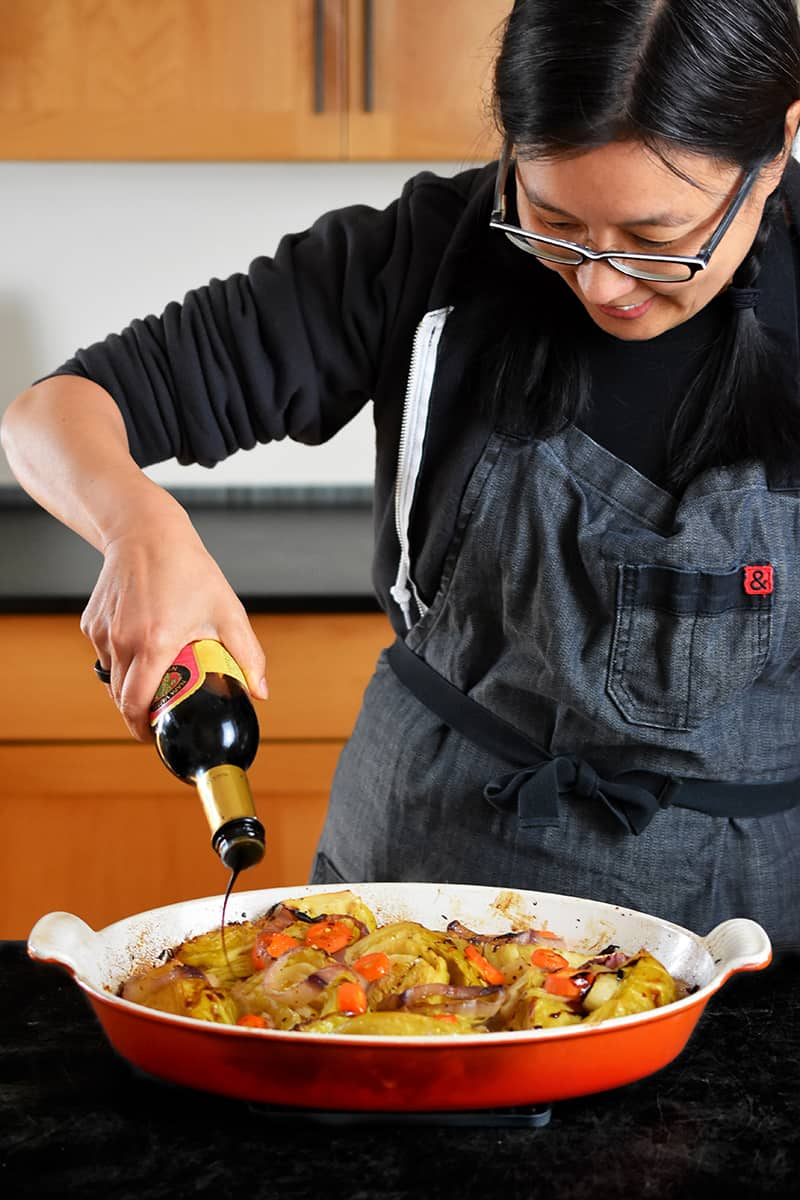 An Asian woman in a gray apron is pouring balsamic vinegar on braised cabbage right out of the oven.