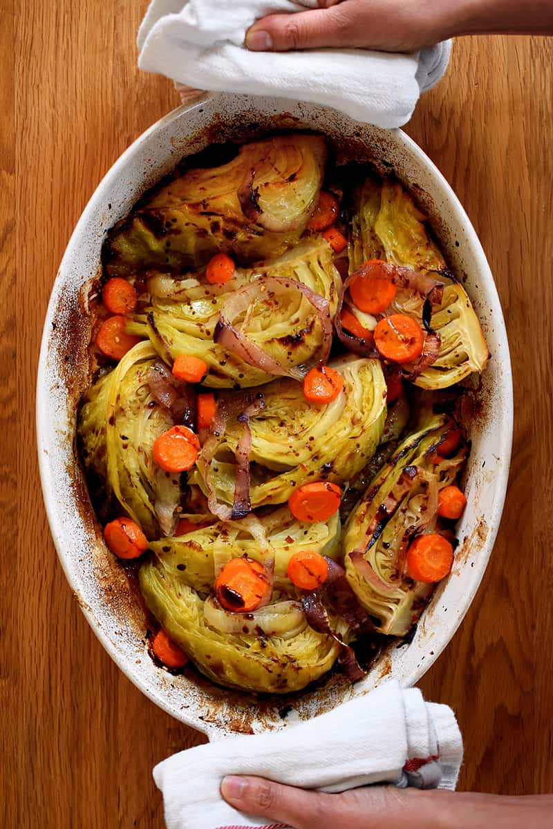 An overhead shot of the world's best braised green cabbage, carrot coins, and sliced onions in an oval casserole pan. Two hands are holding the handles with towels.