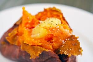 Close up of a baked sweet potato topped with melted ghee, salt, and pepper.