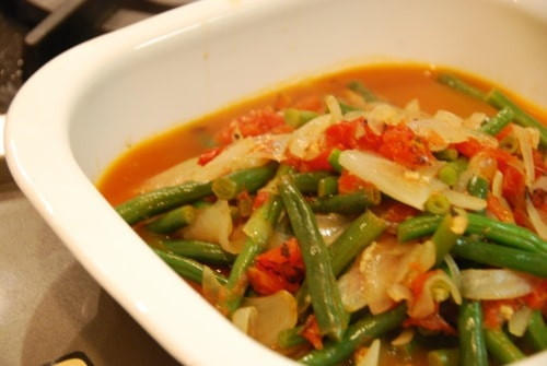 A bowl of paleo braised green beans with tomatoes and onions.