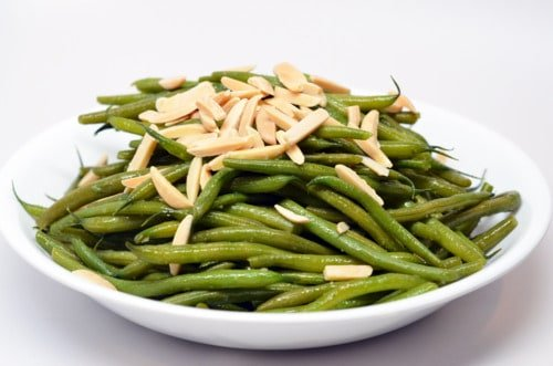 A plate of microwaved green beans in a white bowl topped with slivered almonds.