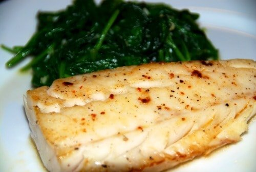 Paleo and Whole30 easy sous vide wild alaskan cod on a plate with steamed spinach.