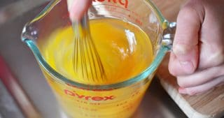 Someone whisking eggs in a Pyrex measure glass.