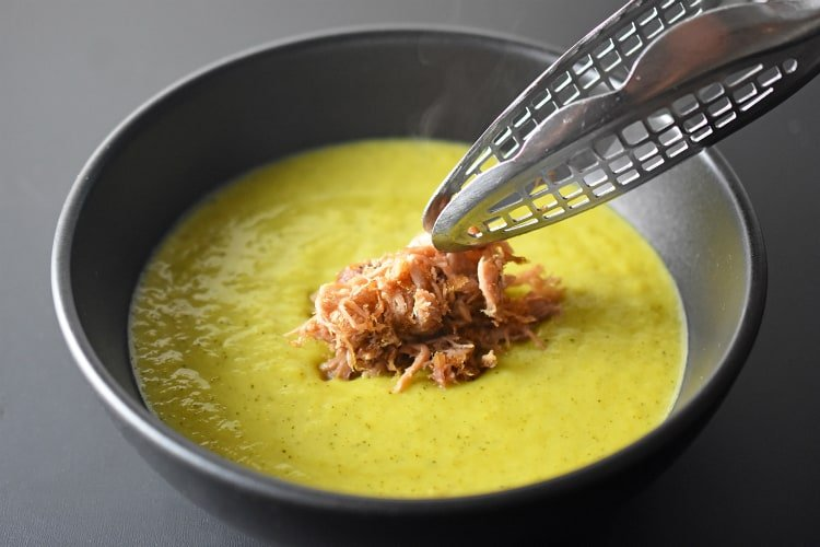 A bowl of paleo and Whole30 Curried Cream of Broccoli Soup topped with crispy Kalua Pig.