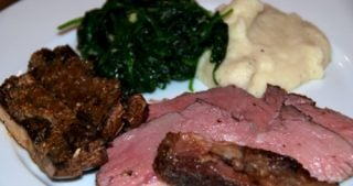 A plate of sous vide mustard and herb seasoned butterflied lamb leg with garlic cauliflower mash and spinach.