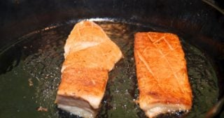 Two sous vide cooked pork bellies frying on a cast iron skillet.