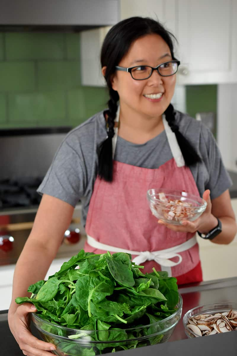 An Asian woman in a red apron is holding a large bowl of raw spinach and sliced bacon.