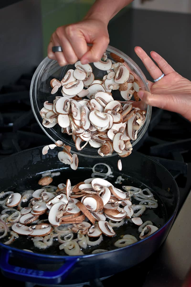 Two hands are dumping a glass bowl filled with thinly sliced cremini mushrooms into a cast iron skillet.