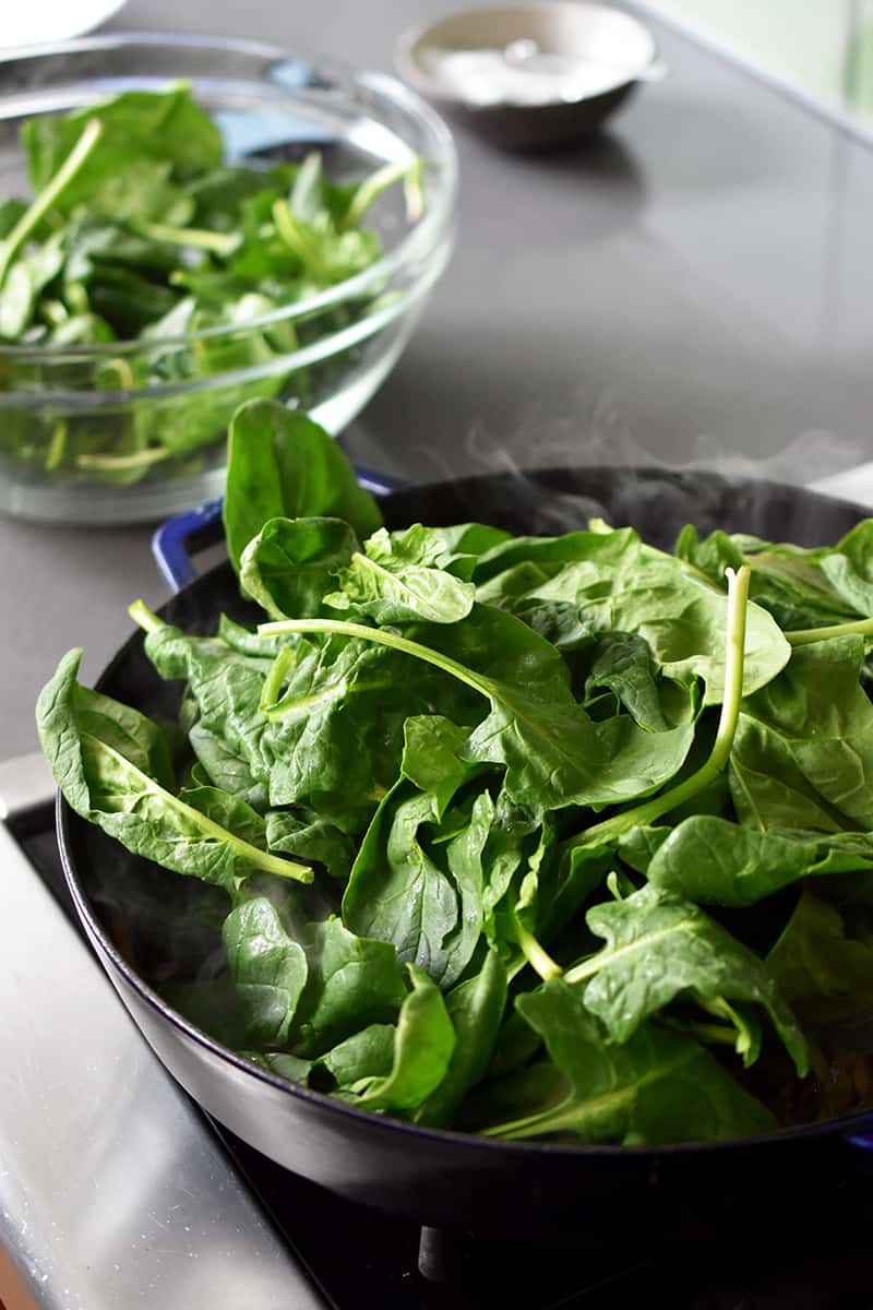 There is a bowl with spinach in it next to a large skillet filled with spinach.
