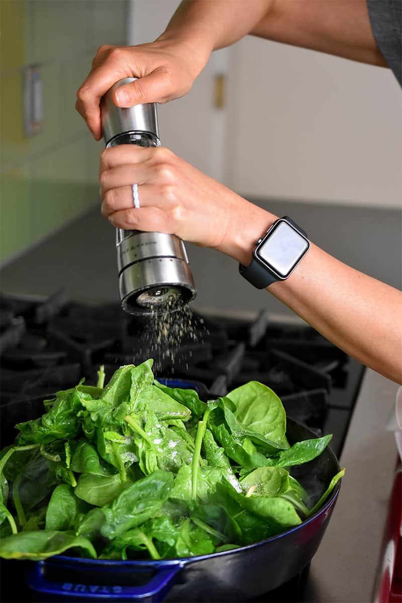 Adding pepper from a pepper mill to a skillet filled with spinach