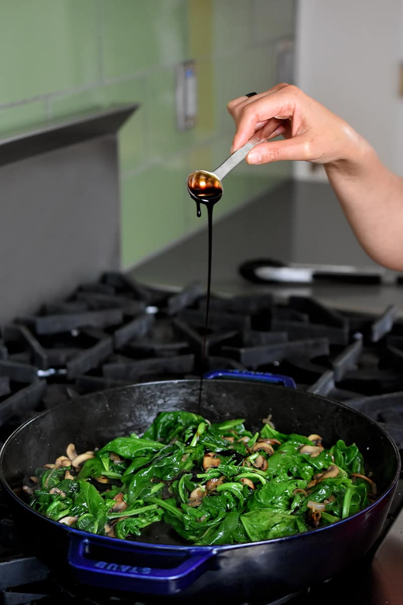 A hand is asking a spoonful of aged balsamic to a pan filled with spinach, mushrooms, and shallots.