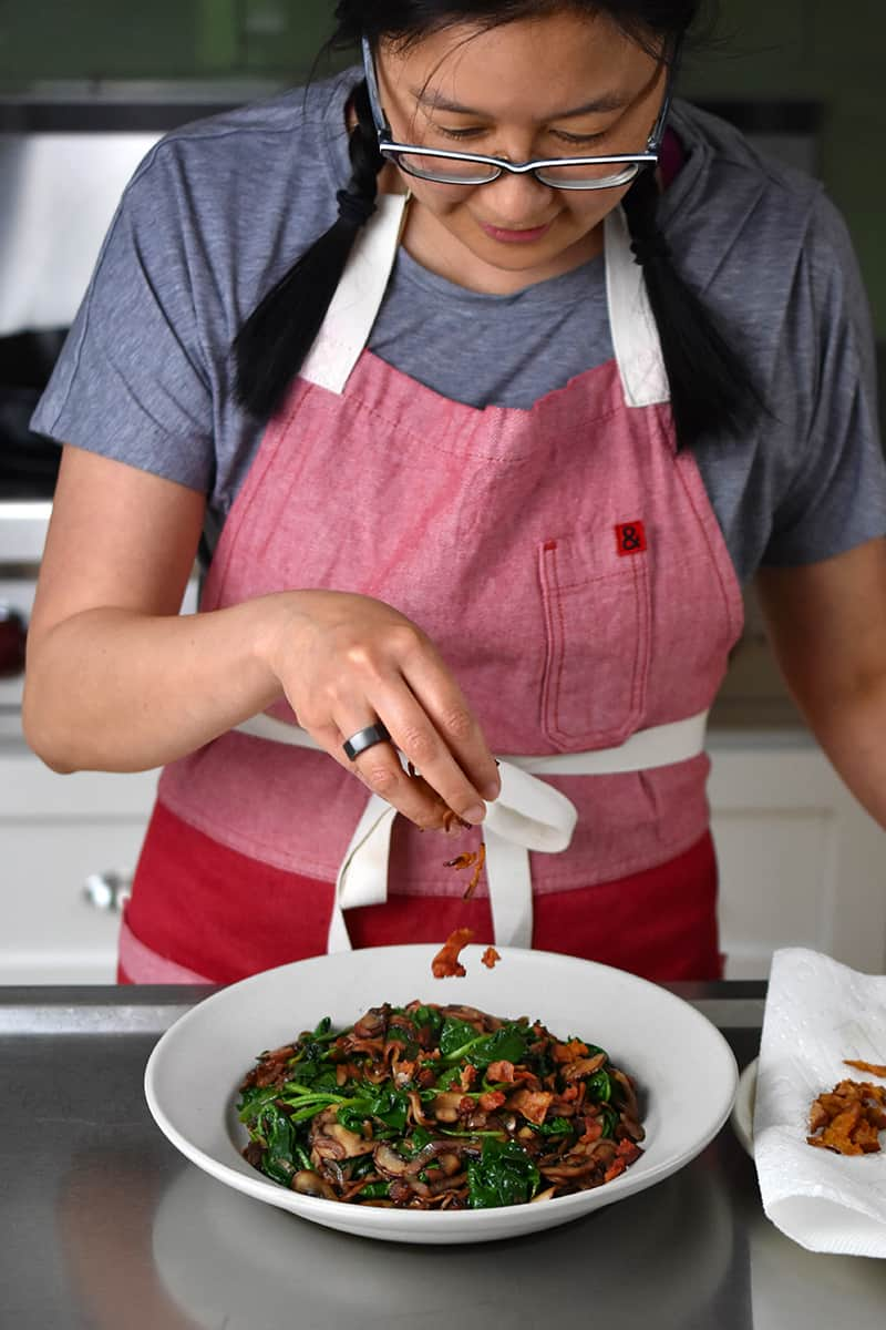 A woman in a red apron is sprinkling crispy bacon bits on top of a bowl filled with sautéed spinach and mushrooms.