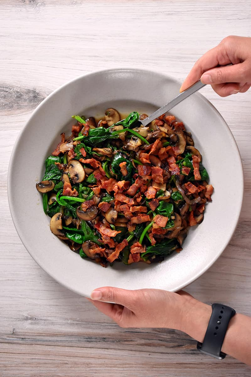 To hands are holding a cream colored bowl filled with sautéed spinach with bacon and mushrooms.