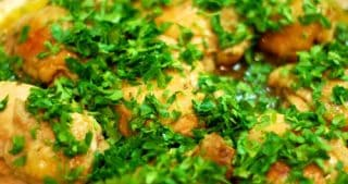 Whole30 roast chicken in a baking dish topped with chopped parsley.