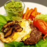 "A plate with a lamb burger on top of a lettuce ""bun"" topped with a fried egg and sautéed shiitake mushrooms and onions."