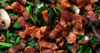 A plate of the paleo dish sautéed spinach with bacon, shallots, and mushrooms.