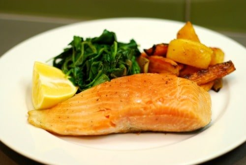 A plate of sous vide wild king salmon with a lemon wedge, sautéed spinach, and carrots.