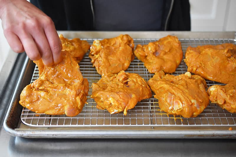 Super Easy Tandoori Chicken thighs are placed in a single layer on a wire rack on a rimmed baking sheet.