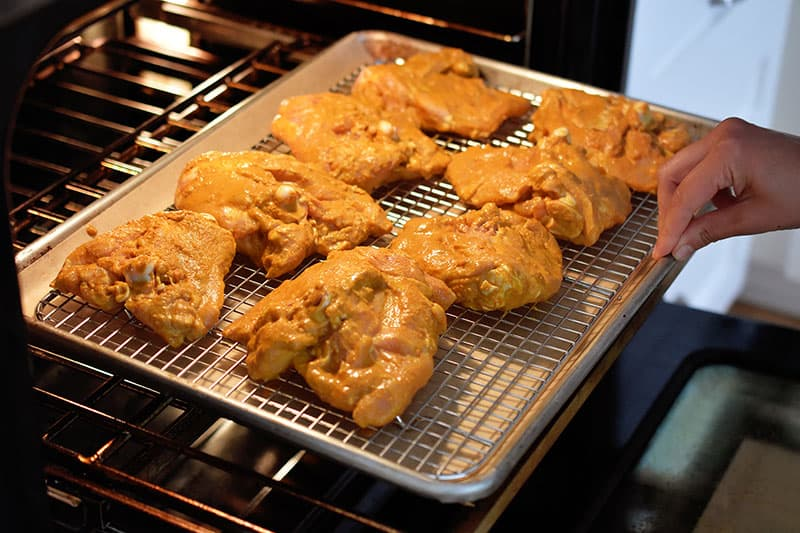 Placing a tray of super easy tandoori chicken into the oven.