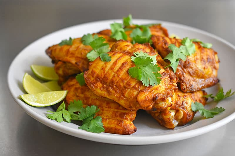 Side view of super easy tandoori chicken topped with cilantro and served with lime wedges.
