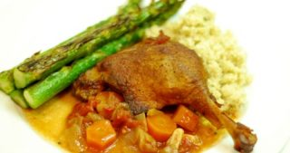 A plate containing braised duck leg, carrots, and asparagus.