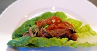 Overnight oven-braised shredded pork in a paleo and whole30 lettuce taco.