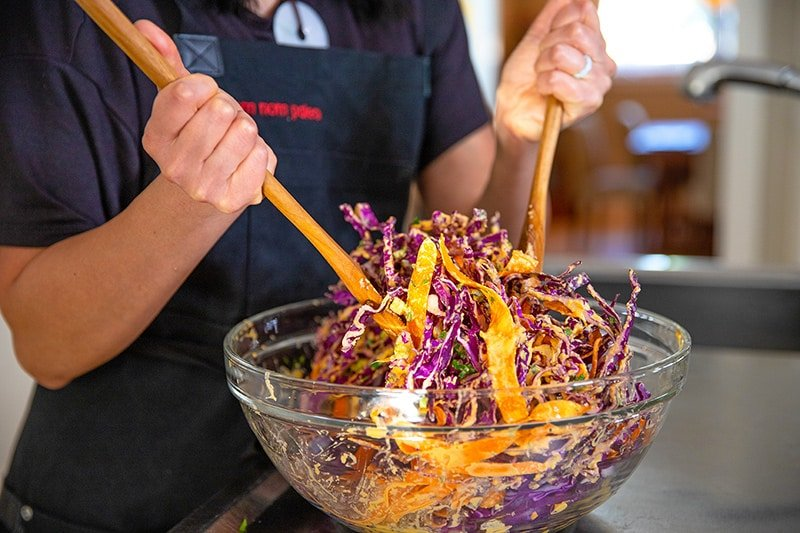 Someone tossing whole30 red cabbage slaw in a large clear bowl with wooden spoons.