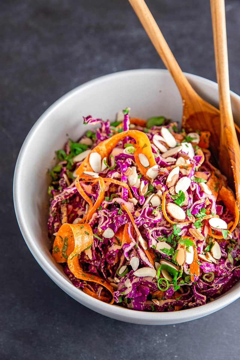 A shot of Whole30 and paleo red cabbage slaw in a large white bowl with two wooden serving spoons inside.