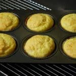 Six cheesy muffins in a muffin tin.
