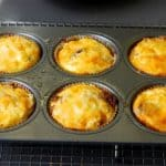 A tray of six mini frittata muffins with cheese and bacon.