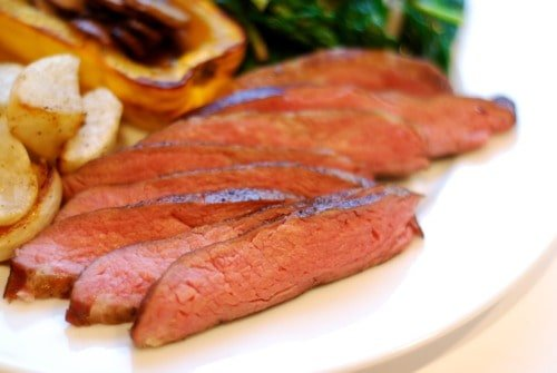 A plate of flank steak cooked sous vide cut up into thin strips.