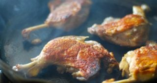 Four duck legs cooking on a cast iron skillet with smoke rising off the ducks.