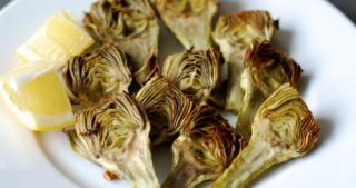 A plate of roasted baby artichokes with lemon.