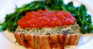 A spinach and mushroom meatloaf topped with bacon is on a plate with cooked spinach and it is topped with marinara sauce.