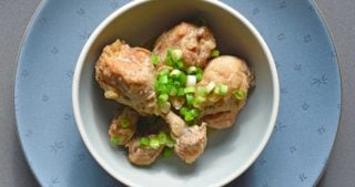 Bowl of lemongrass and coconut chicken drumsticks cooked in a slow cooker.