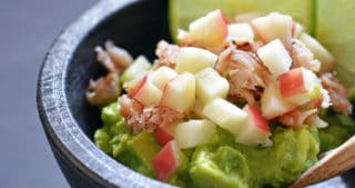 Top view of guacamole topped with lump crab meat, diced apples, and lime slices.