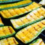 Zucchini grilling on a grill.