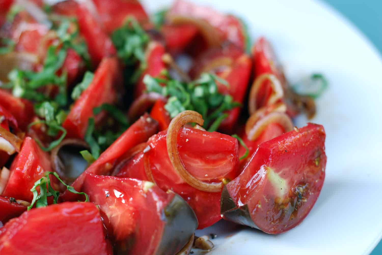 A platter of Tomato and Basil salad on a white plate.