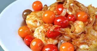 A plate of sautéed shrimp with roasted tomatoes and onions.