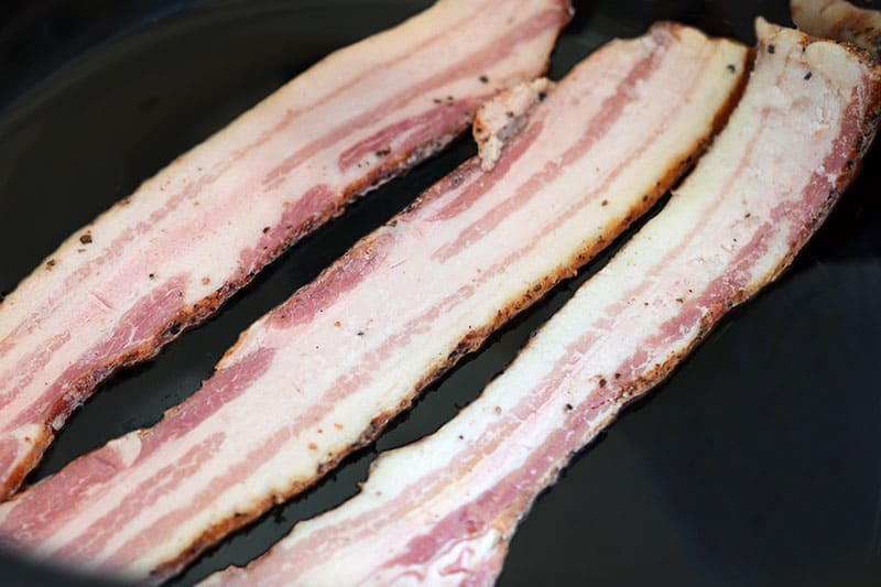 Three slices of raw bacon on the bottom of a slow cooker