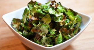 A square bowl is filled with crispy Brussels sprout chips, a paleo and vegan snack