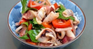 Bowl of grilled calamari with roasted peppers.