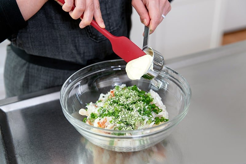 A large glass bowl filled with crab, scallions, coconut flour, seafood seasoning, and mayonnaise.