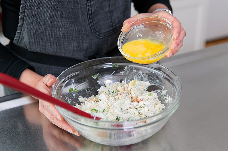 Pouring a whisked egg into the crab cake mixture.